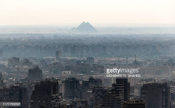 This picture taken on October 23, 2019 from the Cairo Tower in the centre of the Egyptian capital shows a view of the Giza Pyramids in Cairo's twin...