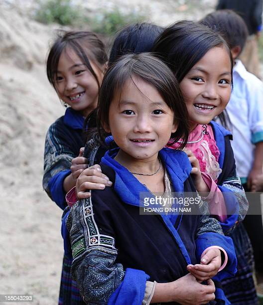 This picture taken on October 24 2012 shows Hmong ethnic pupils looking at visitors at a boarding elementary school in the mountainous district of Mu...