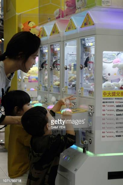 This picture taken on October 24 2018 shows a mother helping her children to operate a claw crane machine in Taipei As Taiwan's economy stagnates...