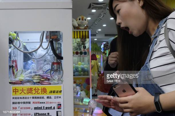 This picture taken on October 24 2018 shows a woman reacting while operating a claw crane machine at a store in Taipei As Taiwan's economy stagnates...