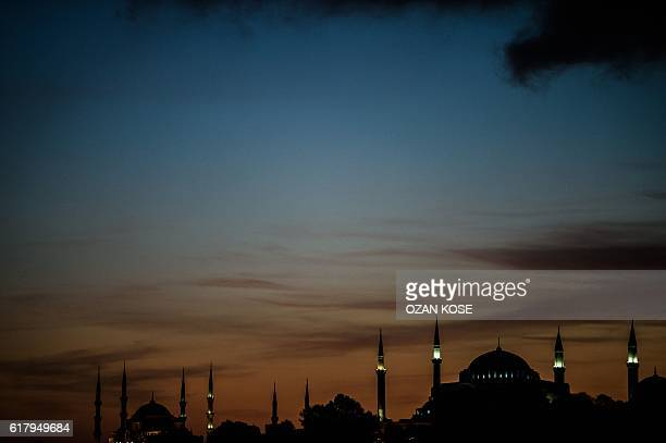 This picture taken on October 25 2016 shows the silhouettes of Sultan Ahmed Mosque and Hagia Sophia at sunset in Istanbul / AFP / OZAN KOSE