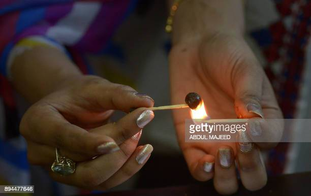 This picture taken on October 25 2017 shows a Pakistani smoker holding a match to a clump of hashish to soften it before mixing it with cigarette...