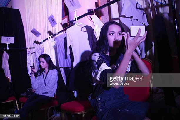 This picture taken on October 26 2014 shows a model preparing backstage before the Hei Lau Collection show during China Fashion Week in Beijing China...