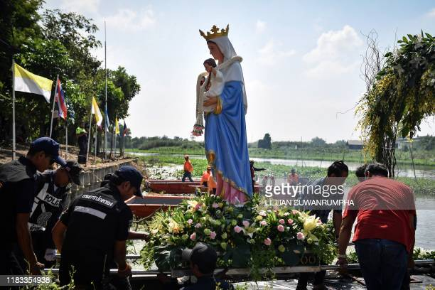 This picture taken on October 26 shows a statue of the Virgin Mary being carried onto a boat for a river procession by Thai Catholics of Vietnamese...
