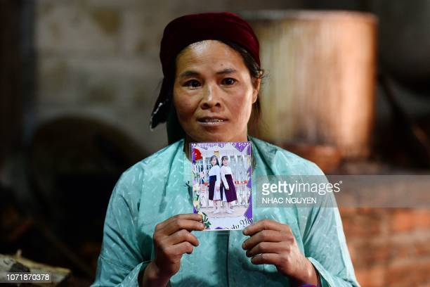 This picture taken on October 27 2018 shows Ly Thi My a Vietnamese mother posing with a photograph of her missing daughter Di at her house in Meo Vac...