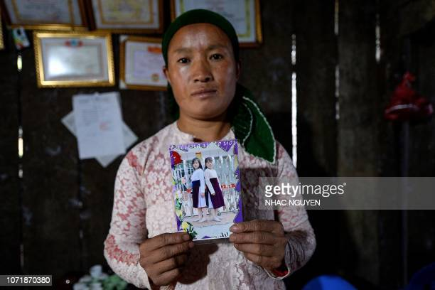 TOPSHOT This picture taken on October 27 2018 shows Vu Thi Dinh a Vietnamese mother posing with a photograph of her missing teenaged daughter Dua at...