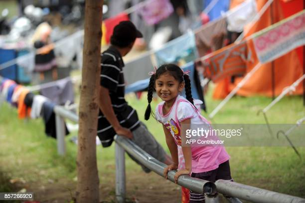 This picture taken on October 3 2017 shows a young girl smiling at an evacuation center in Klungkung on Bali island Mount Agung 75 kilometres from...