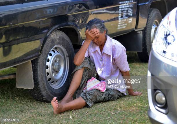 This picture taken on October 3 2017 shows an elderly woman sitting between cars at an evacuation center in Klungkung on Bali island Mount Agung 75...