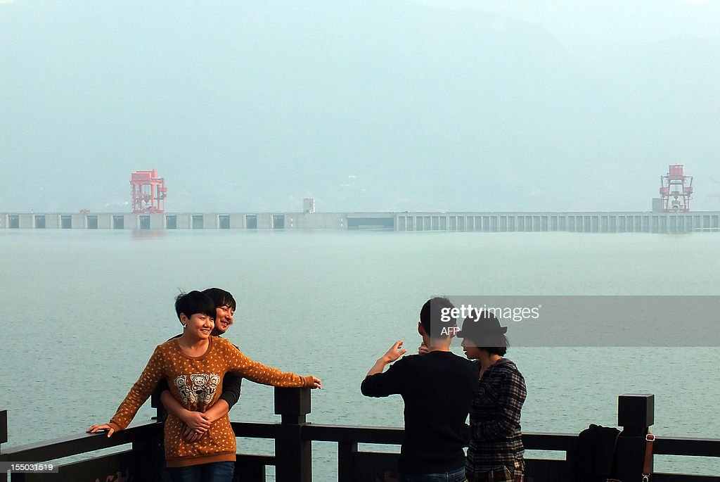 This picture taken on October 30, 2012 shows visitors taking photos at the Three Gorges Dam on the Yangzte River in Yichang, central China's Hubei province. The giant and controversial Three Gorges Dam on China's Yangtze River started from July 4 working at full capacity as the last of its 32 generators went into operation, state news agency Xinhua said. CHINA
