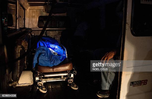 This picture taken on October 30 2016 shows a body bag in a funeral ambulance containing the body of an alleged drug dealer who was gunned down by...