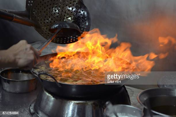 This picture taken on October 30 2017 shows a chef of Shin Yeh restaurant cooking in Taipei From streetside stalls dishing out one dollar bowls of...