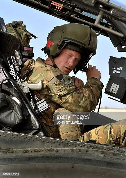 This picture taken on October 31 2012 shows Britain's Prince Harry sitting in the cockpit of an Apache Helicopter at the British controlled...
