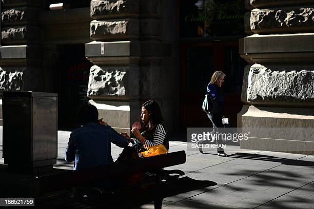 This picture taken on October 31, 2013 shows girls eating their food while sitting on a bench at Martin Place during the lunch hour in the central...