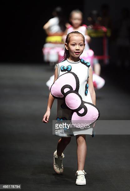 This picture taken on October 31 2015 shows child models parading creations from Hello Kitty and My Melody Comme Tu Es Parentchild Outfit Collection...