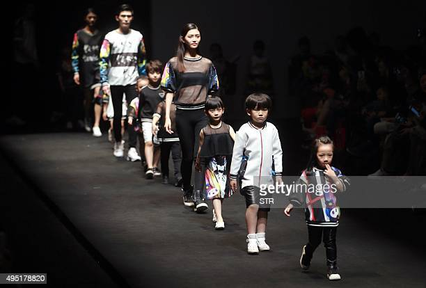 This picture taken on October 31 2015 shows models parading creations from Hello Kitty and My Melody Comme Tu Es Parentchild Outfit Collection at...