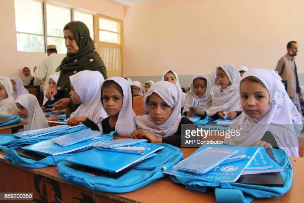 This picture taken on October 8 2017 shows Afghan school girls looking on as they receive pens and bags from the United Nations Children's Fund at a...