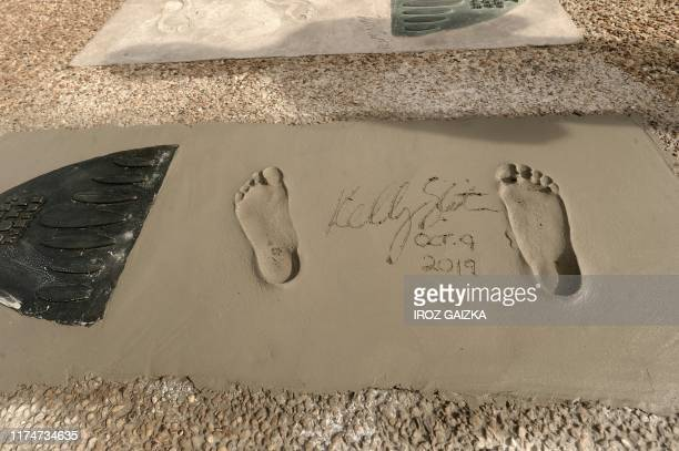 TOPSHOT This picture taken on October 9 2019 shows the American legend surfer Kelly Slater footprints and signature on the Promenade des Sables dOr...