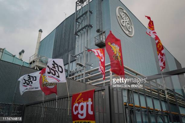 This picture taken on October 9 shows CGT Union flags flutter as employees of US giant General Electric block the main entrance of Belfort plant,...