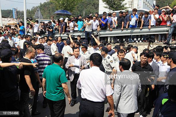This picture taken on September 1 2012 shows police officers lining a road as residents and members of the media gather following the apprehension of...