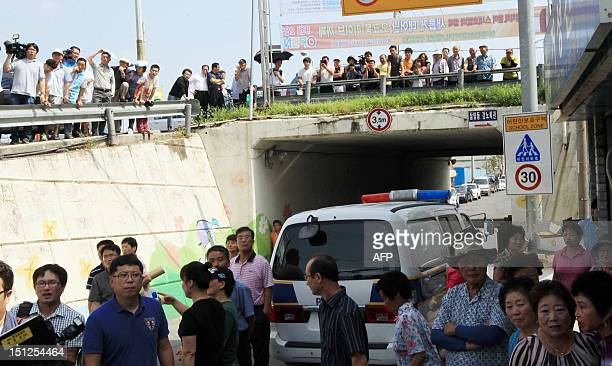 This picture taken on September 1 2012 shows residents and members of the media gathering along a road as a police vehicle drives past following the...