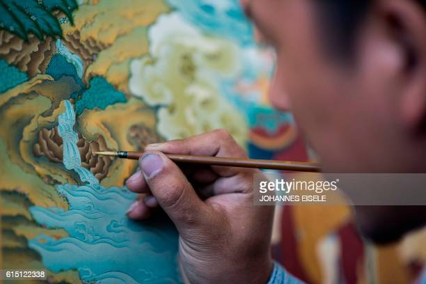 This picture taken on September 10 2016 shows a student painting an example of the medieval Tibetan art of 'thangka' minutely detailed paintings...