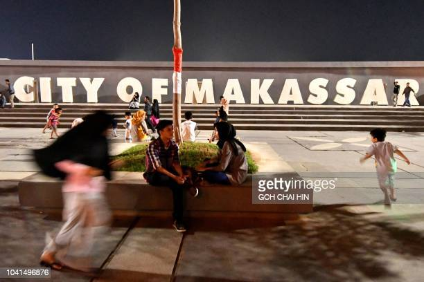 This picture taken on September 10 2018 shows residents at a promenade along Losari Beach in Makassar a port city on eastern Indonesia's Sulawesi...