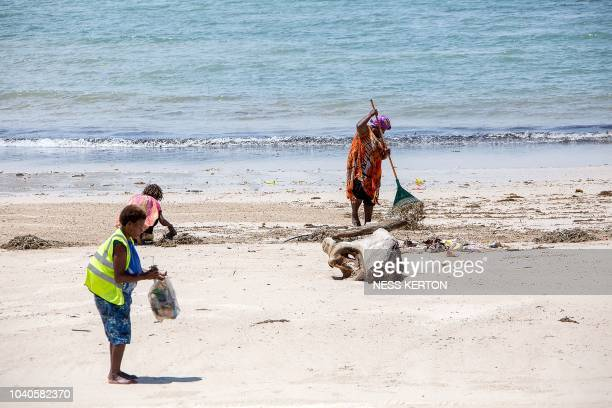 This picture taken on September 10 2018 shows workers cleaning a beach close to the venues of the upcoming AsiaPacific Economic Cooperation summit in...