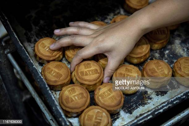 TOPSHOT This picture taken on September 10 2019 shows mooncakes adorned with a popular slogan from recent prodemocracy protests being prepared for...