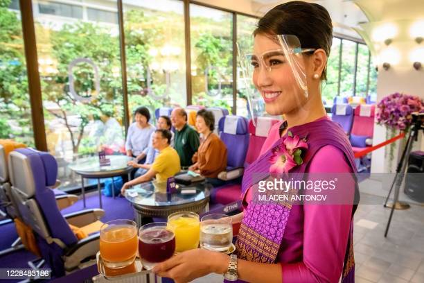 This picture taken on September 10 2020 shows a Thai Airways flight attendant wearing a face shield as she serves drinks at a popup airplanethemed...