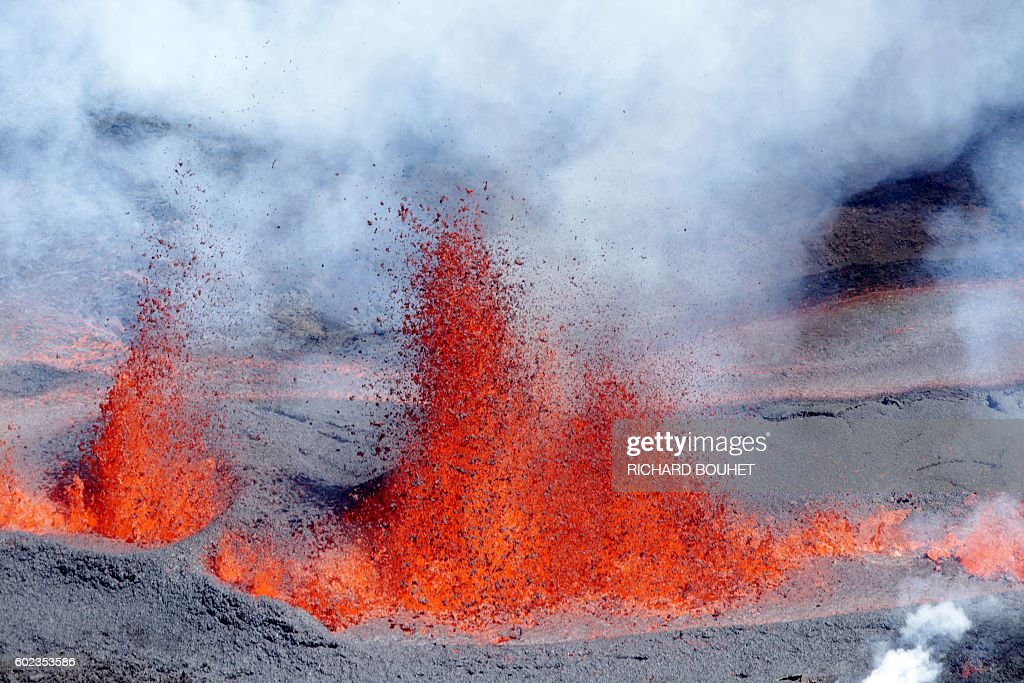 TOPSHOT - This picture taken on September 11, 2016 shows a molten lava spray after a volcanic eruption from 'The Peak of the Furnace' (Le Piton de la Fournaise) in the eastern side of the on the French Indian Ocean island of La Reunion. / AFP / Richard BOUHET
