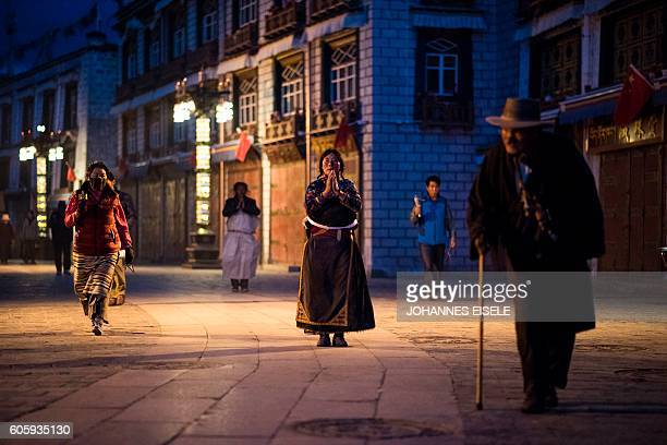 TOPSHOT This picture taken on September 11 2016 shows pilgrims praying and prostrating outside the Jokhang Temple in the regional capital Lhasa in...