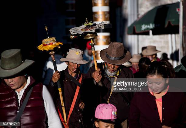 TOPSHOT This picture taken on September 11 2016 shows pilgrims spinning their prayer wheels outside the Jokhang Temple in the regional capital Lhasa...