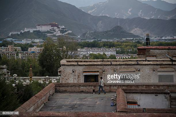 This picture taken on September 11 2016 shows the Potala Palace and a man walking on the rooftop of a building of the Sera Monastery in the regional...