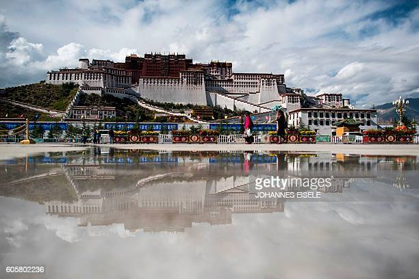 This picture taken on September 11, 2016 shows tourists in front of the iconic Potala Palace in the regional capital Lhasa, in China's Tibet...