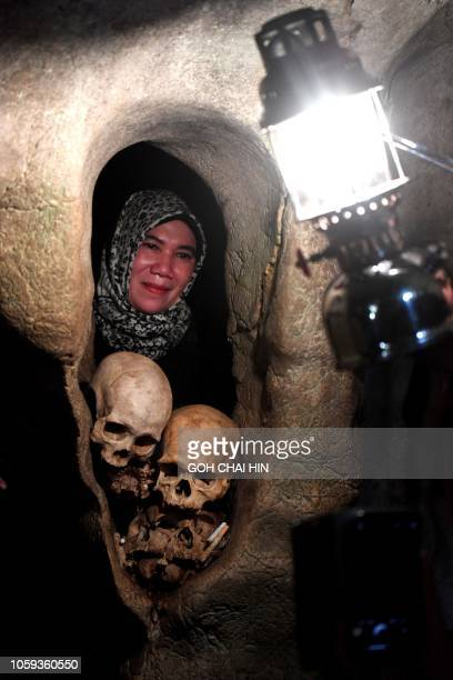 This picture taken on September 11 2018 shows a visitor poses with the remains of bodies interned in a burial cave in Londa in Tana Toraja regency...