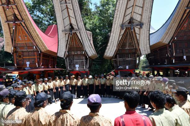 This picture taken on September 12 2018 shows Torajan villagers performing a dance during a funeral ceremony known as Rambu Solo in Londa in Tana...