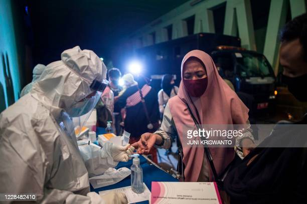 This picture taken on September 12, 2020 shows a woman having her blood sample taken to be tested for the COVID-19 coronavirus in Surabaya, East Java.