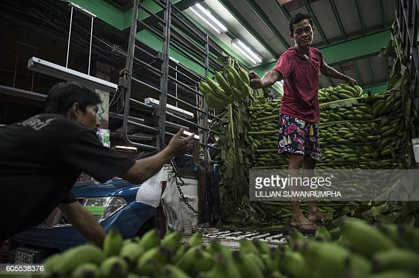 This picture taken on September 13 2016 shows men unpacking unripe bananas from a truck in Bangkok / AFP / LILLIAN SUWANRUMPHA