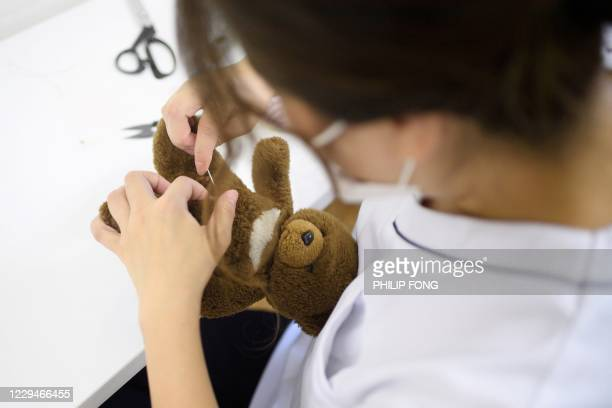 This picture taken on September 13, 2020 shows founder Natsumi Hakozaki doing a quick repair for a stuffed toy bear at Natsumi Clinic in Tokyo. - The...