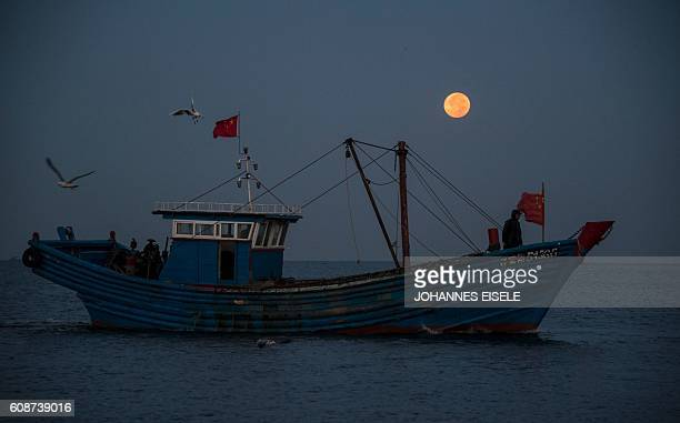This picture taken on September 17 2016 shows fisherman on their boat in front of the full moon in Xianrendao in China's northeastern Liaoning...