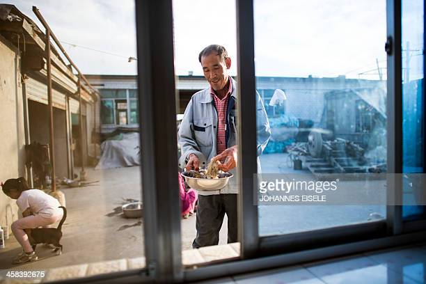 This picture taken on September 18 2016 shows Qin Yusheng preparing sea food for dinner with his family in Xianrendao next to Yingkou City in China's...