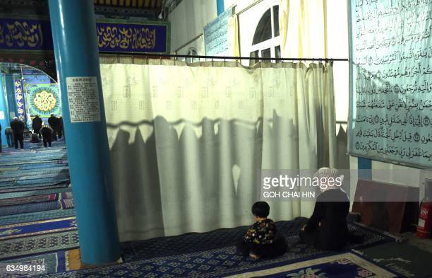 This picture taken on September 19 2015 shows a Chinese Hui Muslim woman and her child praying behind a curtain during evening prayers at the Great...