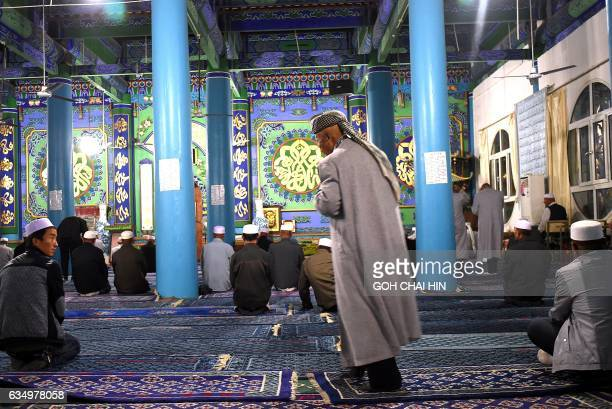 This picture taken on September 19 2015 shows Chinese Hui Muslim men arriving for evening prayers at the Great Mosque of Tongxin located some 200 kms...