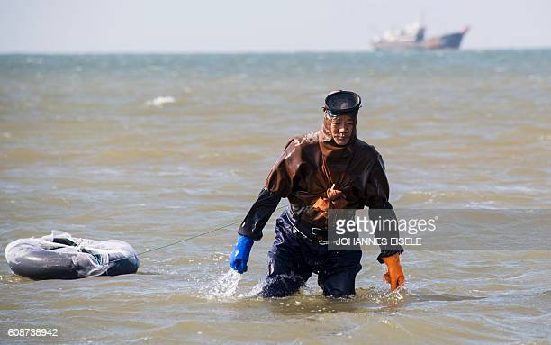 This picture taken on September 19 2016 shows a man in a simple diving suit wading in the sea in Xianrendao in China's northeastern Liaoning province...