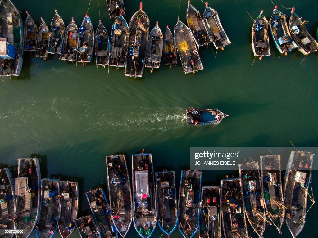 TOPSHOT - This picture taken on September 19, 2016 shows people onboard fishing boats heading out to sea in order to catch crabs, in Xianrendao in China's northeastern Liaoning province. /