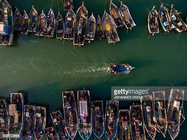 TOPSHOT This picture taken on September 19 2016 shows people onboard fishing boats heading out to sea in order to catch crabs in Xianrendao in...