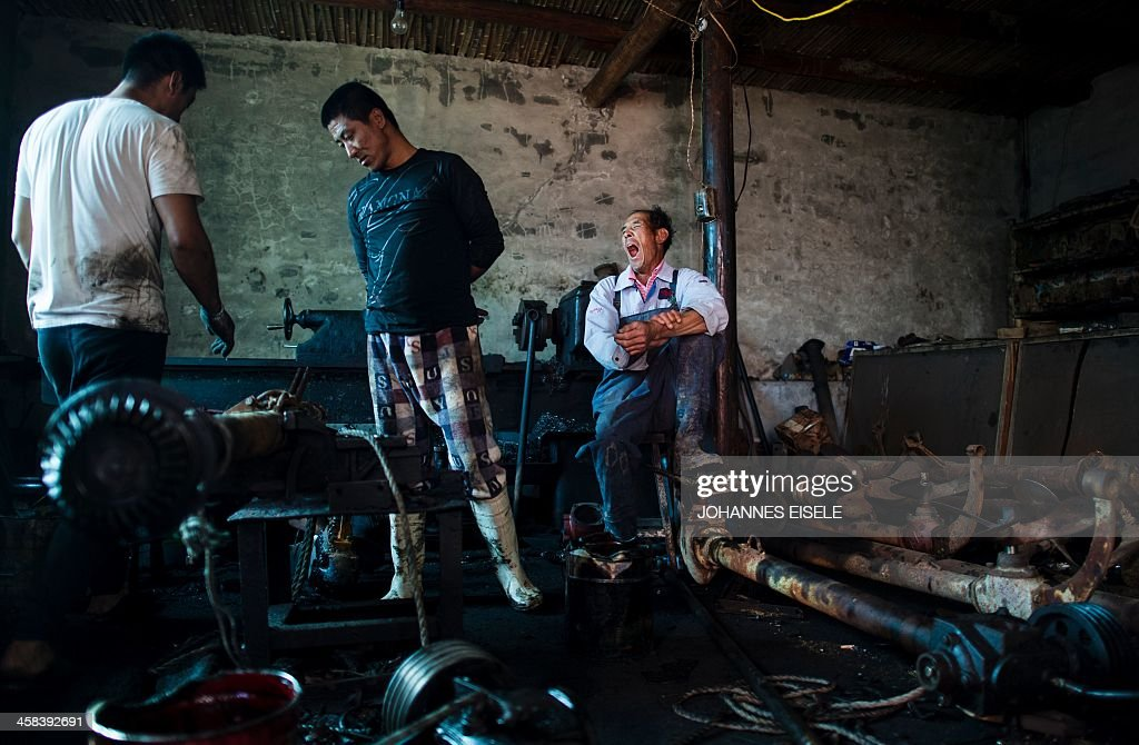 This picture taken on September 19, 2016 shows Qin Yusheng (R) waiting for a ship propeller being repaired in order to return it to the boat with his horse cart in Xianrendao next to Yingkou City in China's northeastern Liaoning province. For decades, equine-powered carts have trundled through the shallow waters off the peninsula near Xianrendao to meet shallow-keeled trawlers piled high with jellyfish, which teem in the waters of the Yellow Sea. Now Qin, 55, and his last two mules are ready to retire, as the area's traditional way of life slides into history. / AFP / JOHANNES