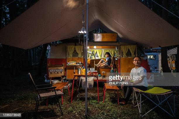 This picture taken on September 19, 2021 shows campervan enthusiast Takayuki Minagawa and his son Rintaro Minagawa sitting in a 1964 Volkswagen Type...