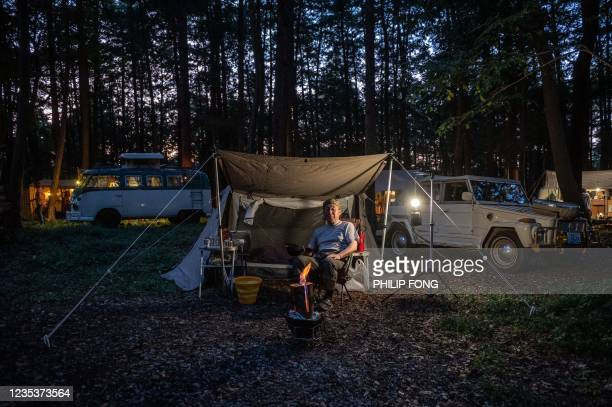 This picture taken on September 19, 2021 shows campervan enthusiast Nobuyuki Ito taking a rest in front of his 1974 Volkswagen Type 181 - Thing at a...