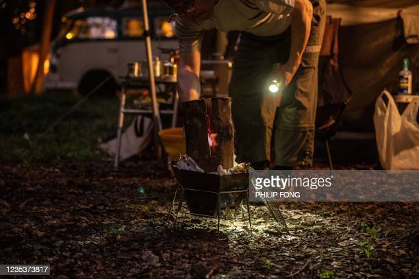 This picture taken on September 19, 2021 shows campervan enthusiast Nobuyuki Ito setting a fire in front of his 1974 Volkswagen Type 181 - Thing at a...